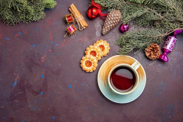 Вид сверху чашка чая с печеньем на темном столе, чайное печенье, бисквитный торт
