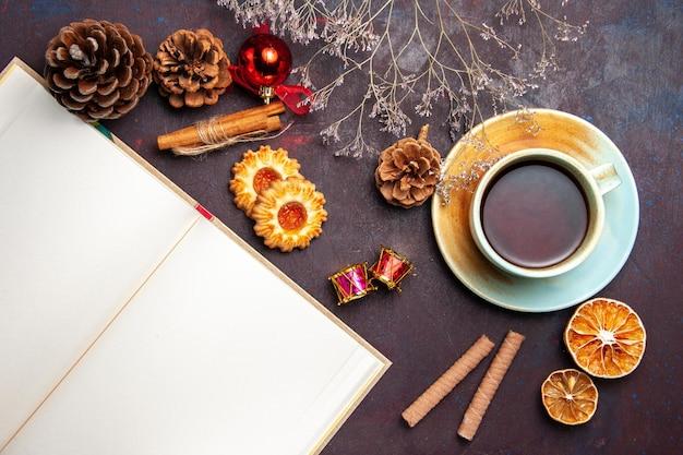 Вид сверху чашка чая с печеньем на темном пространстве