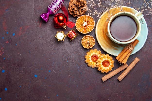 暗いスペースにクッキーを入れたお茶のトップビューカップ