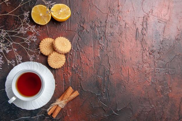 暗いテーブルの上のクッキーとお茶のトップビューカップティーグラス写真ビスケット甘い