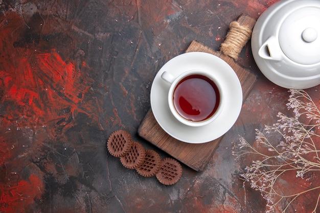 暗いテーブルの上のクッキーとお茶のトップビューカップ