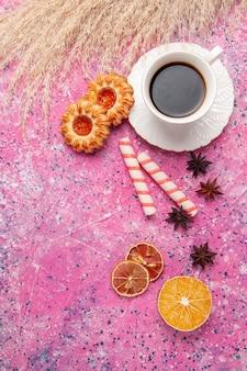 ピンクの机の上のクッキーとお茶のトップビューカップクッキービスケットシュガー甘い色