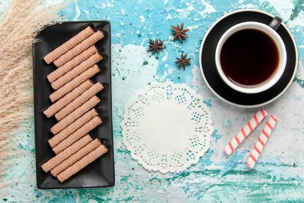 青い表面にクッキーとお茶のトップビューカップ