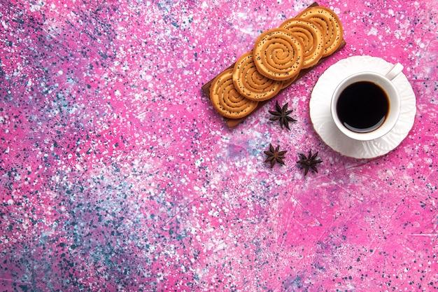 Вид сверху чашка чая с печеньем на светло-розовом столе.