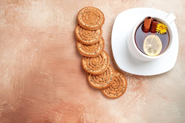 白いテーブルの上のクッキーとお茶のトップビューカップレモンティービスケット