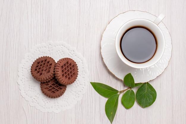 白いテーブル シュガー ティー クッキー スウィート ビスケットにクッキーとお茶のトップ ビュー カップ