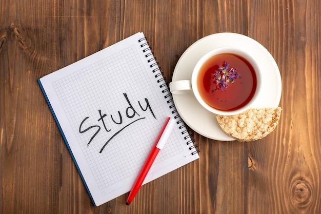 茶色の机の上にコピーブックと鉛筆とお茶のトップビューカップ