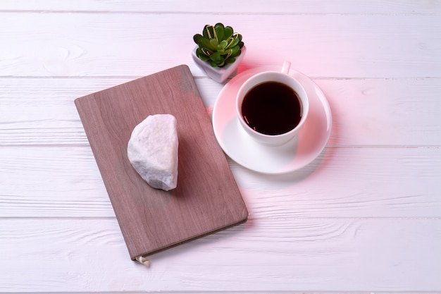 Чашка чая взгляда сверху с тетрадью и планом. фон белый стол.