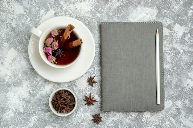 白い背景の上のコピーブックとお茶のトップビューカップお茶は熱い甘い砂糖の朝食を飲みます