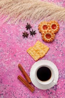 Вид сверху чашка чая с крекерами и печеньем на розовом столе.