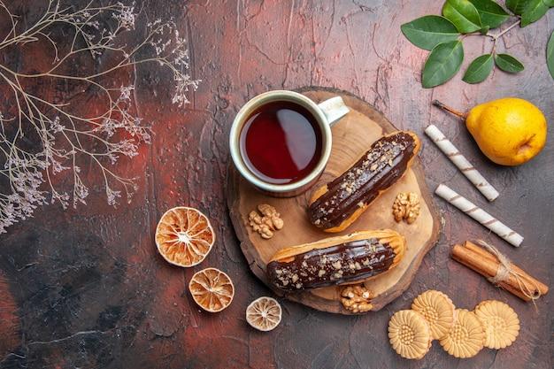 Вид сверху чашка чая с вкусными шоколадными эклерами на темном столовом торте, сладкий десерт
