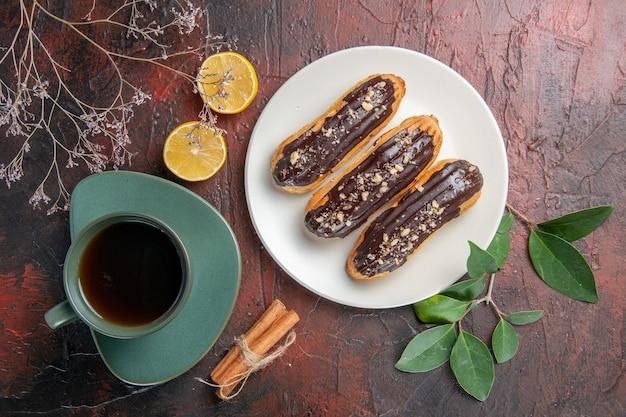 ダークテーブルシュガービスケットデザートスウィートにおいしいエクレアとお茶のトップビューカップ