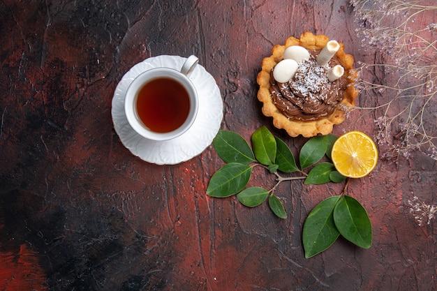 暗いテーブルのクッキーデザートビスケットにおいしい小さなケーキとお茶のトップビューカップ