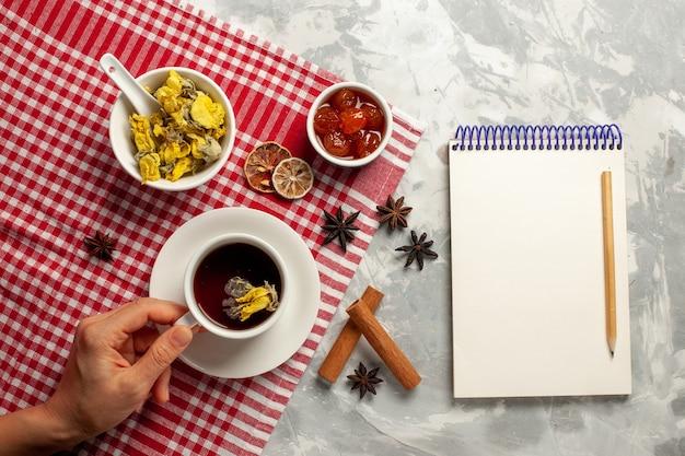 白い机の上のデザートとさまざまなジャムとお茶のトップビューカップフルーツジャムティースイートシュガー