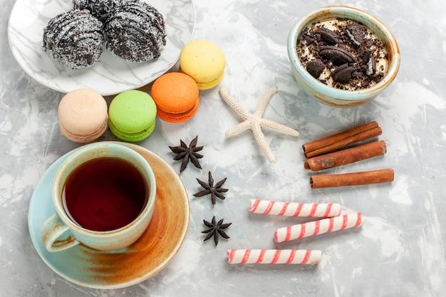 Вид сверху чашка чая с десертными макаронами и шоколадными тортами на белом столе, выпечка торта, бисквитного сахара, сладкого пирога