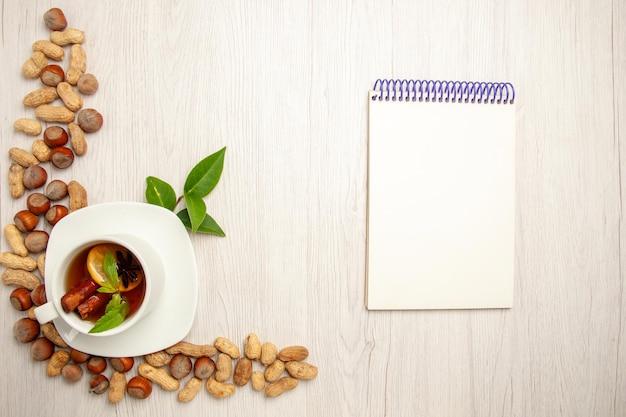 白い机の色のお茶のフルーツセレモニーナッツにさまざまなナッツとお茶のトップビューカップ