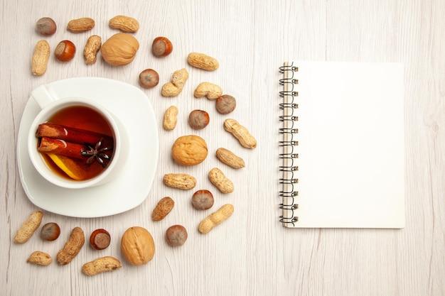흰색 표면 너트 땅콩 차 스낵에 다른 견과류와 함께 차의 상위 뷰 컵