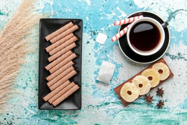 青い机の上に乾燥パイナップルリングとクッキーとお茶のトップビューカップ