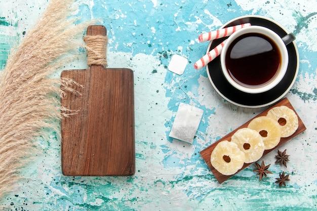 青い机の上に乾燥パイナップルリングとお茶のトップビューカップ