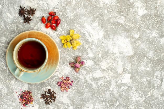 白い背景の上のドライフラワーとお茶のトップビューカップお茶は花の味を飲みます