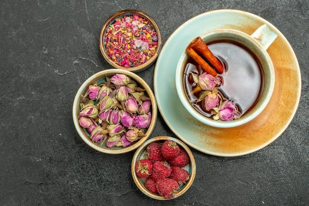 어두운 배경에 꽃과 나무 딸기와 차의 상위 뷰 컵 차 과일 음료 맛 꽃