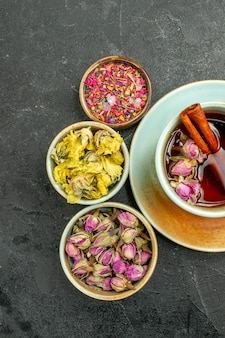 濃い灰色の背景のお茶の飲み物の色の儀式に花とお茶のトップビューカップ