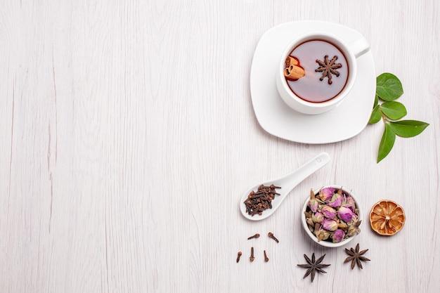 흰색 배경에 꽃과 차의 상위 뷰 컵 과일 차 베리 쿠키 케이크