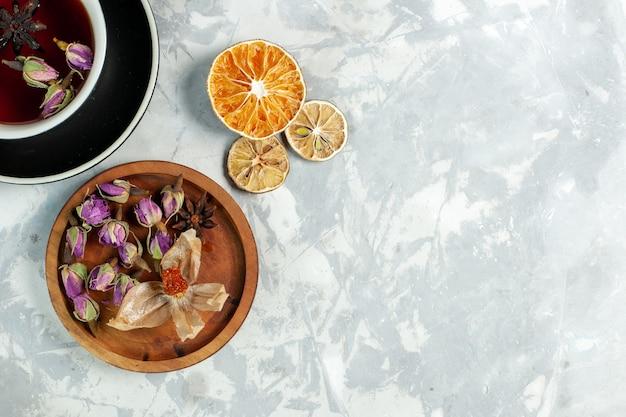 흰 벽에 꽃과 차 한잔의 상위 뷰 차 음료 꽃 레몬