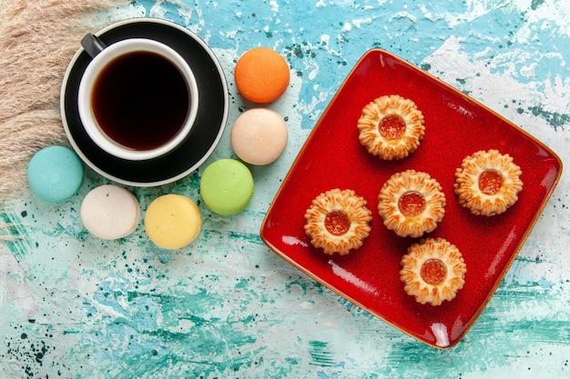 Вид сверху чашка чая с французскими макаронами и печеньем на синей поверхности