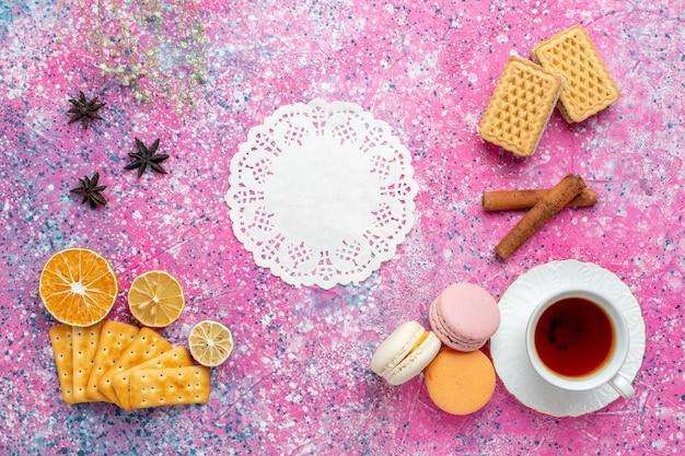 淡いピンクの机の上にフレンチマカロンとクラッカーとお茶のトップビューカップ