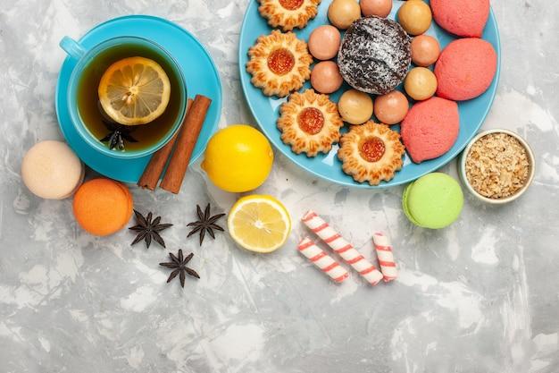 흰색 표면에 프랑스 마카롱 쿠키와 케이크와 차의 상위 뷰 컵