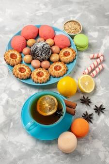 흰색 표면에 프랑스 macarons 작은 쿠키와 케이크와 차의 상위 뷰 컵