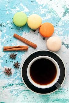 青い表面にフレンチマカロンとお茶のトップビューカップ