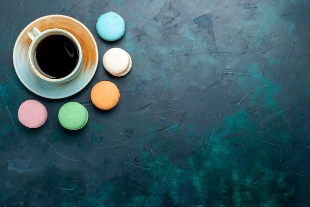 Вид сверху чашка чая с французскими макаронами на темно-синем фоне, выпечка, пирог, сахар, сладкий чай