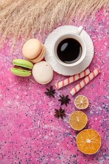 ピンクのデスクケーキビスケット甘い砂糖のパイにフレンチマカロンとお茶のトップビューカップ