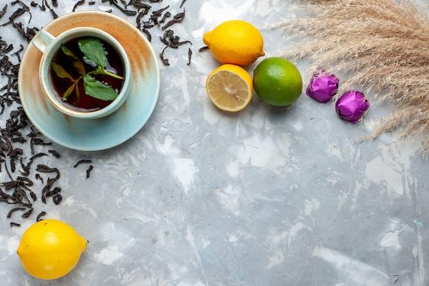 Вид сверху чашка чая со свежими сушеными чайными зернами, конфетами и лимоном на светлом столе, чайный напиток на завтрак