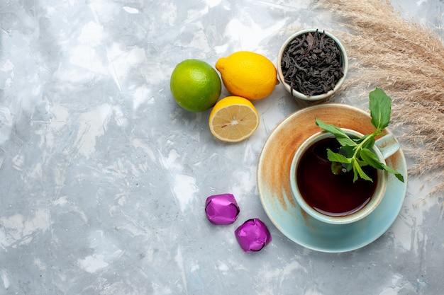 Вид сверху чашка чая со свежими лимонными конфетами и сушеным чаем на светлом столе, чай, фрукты, цитрусовые