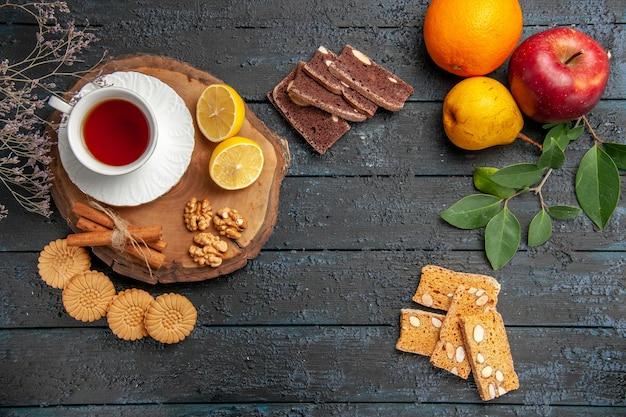暗いテーブルの上の果物やお菓子とお茶のトップビューカップ