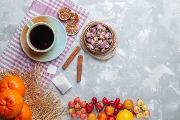 Вид сверху чашка чая с фруктами на белом столе, торт, бисквит, сладкая выпечка