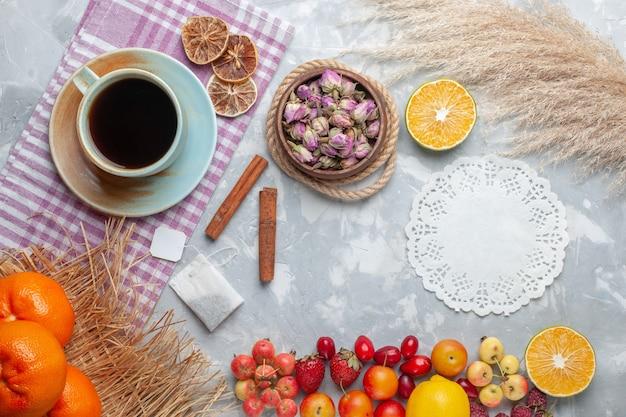 白い机の上の果物とお茶のトップビューカップフルーツ新鮮なまろやかなお茶レモン