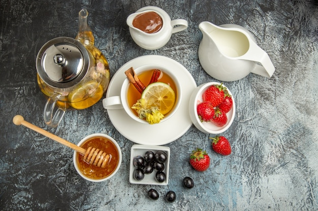 暗い表面の朝の朝食の食べ物に蜂蜜オリーブとフルーツとお茶のトップビューカップ