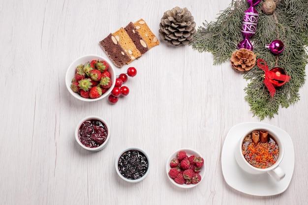 白いテーブルの上のジャムケーキのスライスとフルーツとお茶のトップビューカップフルーツティーゼリー色のクッキー
