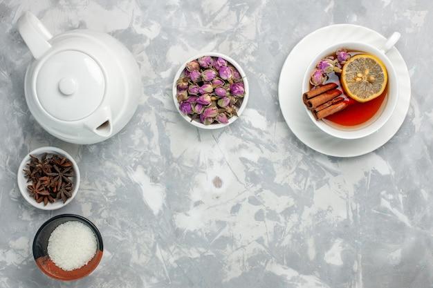 Вид сверху чашка чая с чайником и цветами на белой поверхности