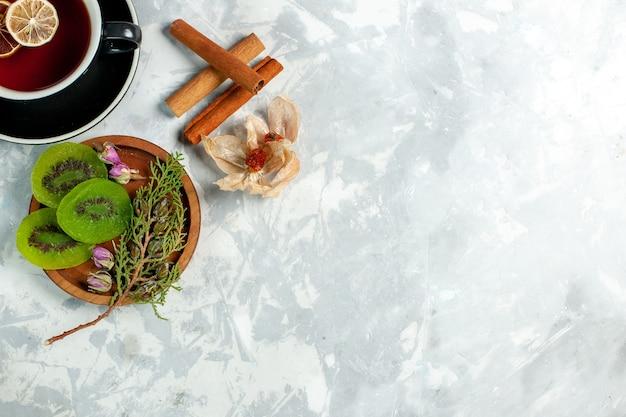 Вид сверху чашка чая с ломтиками киви и корицей на белой стене чайный напиток цветы лимон