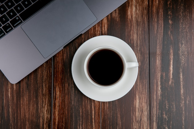 木製の背景上のラップトップとお茶のトップビューカップ