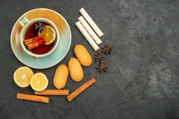 Вид сверху чашка чая с лимоном и печеньем на темном фоне