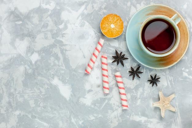 Вид сверху чашка чая с лимоном и конфетами на светлом белом фоне конфеты фруктовый сладкий чай