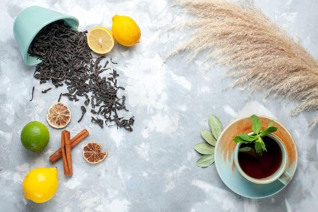 Вид сверху чашка чая с лимоном и корицей на светлом столе, чай сухого цвета из цитрусовых
