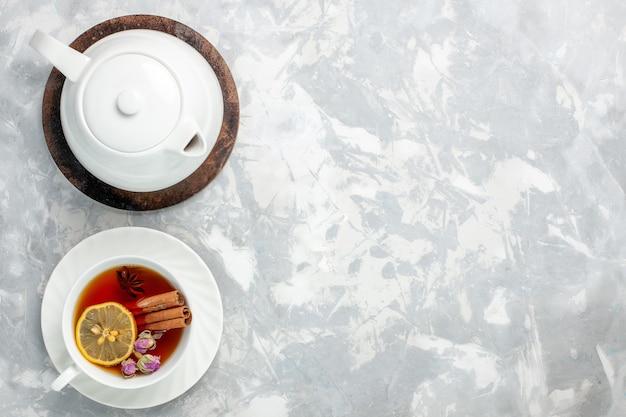 밝은 흰색 표면에 레몬과 계피와 차의 상위 뷰 컵