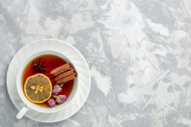 흰색 표면에 레몬과 계피와 차의 상위 뷰 컵